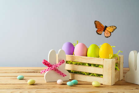 Easter holiday concept with colorful Easter eggs in box and bunny ears on wooden table