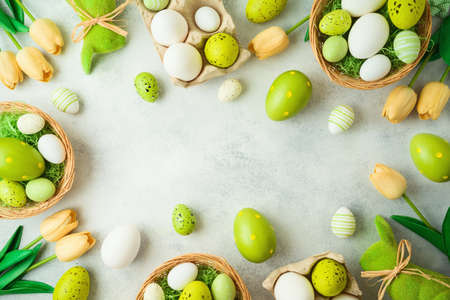 Easter holiday concept with Easter eggs and tulip flowers decor on gray background 免版税图像