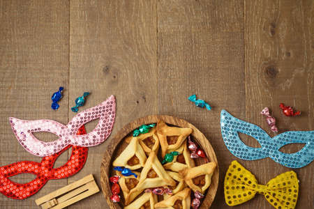 Jewish holiday Purim concept with hamantaschen cookies in wooden plate and carnival mask on table background 免版税图像