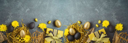 Easter holiday concept with golden Easter eggs and gift box on dark background 免版税图像