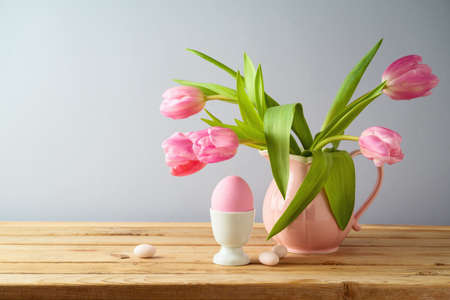 Easter holiday concept with beautiful tulip flowers and pink Easter egg on wooden table