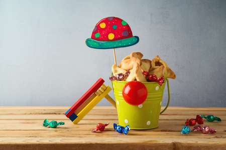 Jewish holiday Purim concept with hamantaschen cookies in bucket with clown nose and hat on wooden table