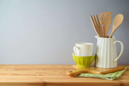 Kitchen utensils and dishware on wooden table. Kitchen interior spring background