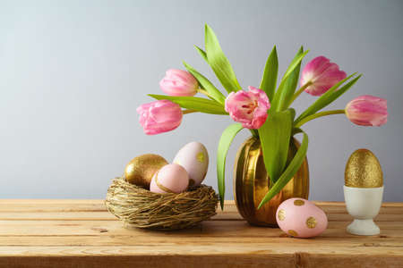 Easter holiday concept with beautiful tulip flowers, pink and golden eggs on wooden table