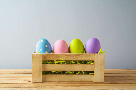 Easter holiday concept with colorful Easter eggs in box  on wooden table