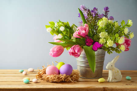 Easter holiday concept with Easter eggs and beautiful tulip flowers bouquet on wooden table
