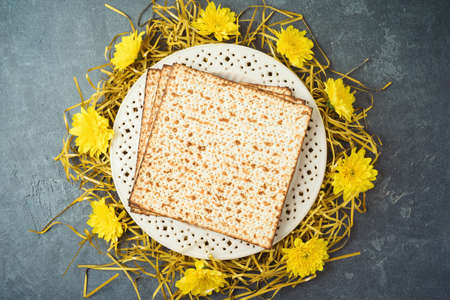 Jewish holiday Passover concept with matzah, seder plate and golden decorations on dark background