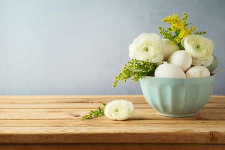 Easter holiday concept with  eggs and flowers in bowl  on wooden table
