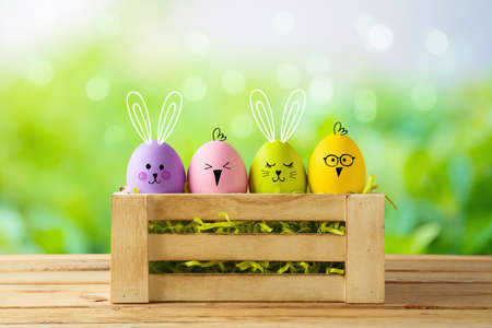 Easter holiday concept with colorful Easter eggs as cute bunny and chicken characters in box on wooden table over green bokeh background