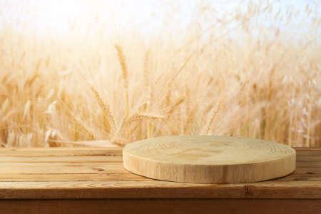 Empty wooden log on rustic table over wheat field background. Jewish holiday Shavuot mock up for design and product display. Stockfoto