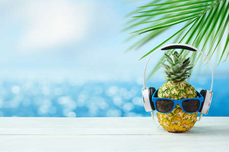 Pineapple with headphones and sunglasses on wooden table over bokeh sea beach background. Summer holidays vacation and beach party concept.