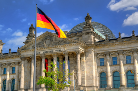 The Reichstag building in Berlin. Flag of the Federal Republic of Germany is waving in front of the national german parliament.