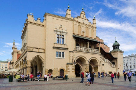 CRACOW, POLAND - AUGUST 16, 2014: Tourists visiting the main market square in Cracow (Poland), which is one of the most famous and beautiful in Europe. Cloth Hall (Sukiennice) in Cracow.