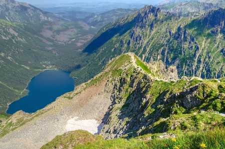 morskie: Lake and ridge in mountains. Morskie Oko (Eye of the Sea) and trail leading via a exposed ridge section, called Kazalnica, High Tatra Mountains, Poland.