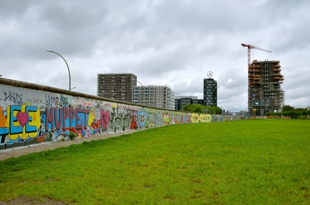 mauer: BERLIN, GERMANY - MAY 2, 2014: The Berlin Wall (Berliner Mauer) in Germany with high-rise buildings at the background. Barrier constructed in 1961, that completely cut off West Berlin from East Berlin, demolished in 1989.