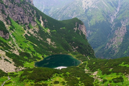 Lake in summer mountains. Picturesque view stretches over emerald pond and steep hillside in Tatra mountains, Slovakia. photo