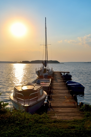 Sailing yacht and jetty. Empty wooden jetty with moored boats on the lake shore at the sunrise in Mazury region, Poland.