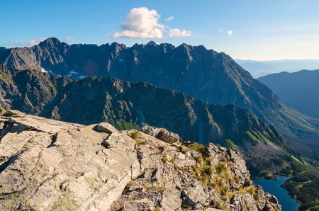 Mountain landscape. Picturesque view stretches over mountain ridge, high rocky summits and lake in Tatras. photo