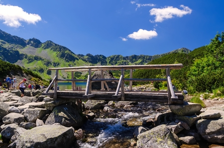 mountainscape: Vacation in polish mountains. Tourists resting by the footbridge over stream in Five Pond Valley in the Tatra mountains Poland. Stock Photo