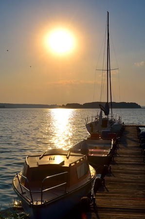 Sailing yacht and a jetty. Empty wooden jetty with moored boats on the lake shore at the sunrise in Masuria region Poland. photo