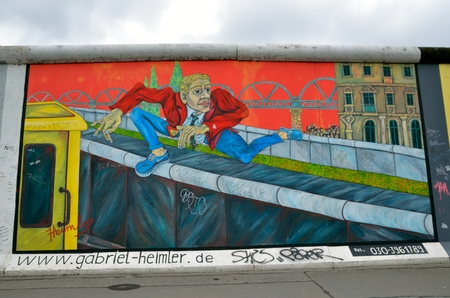 iron curtains: BERLIN GERMANY MAY 2 2014: The Berlin Wall Berliner Mauer in Germany. Colour Graffiti on the wall man climbing over the barrier constructed in 1961 That completely cut off West Berlin from East Berlin demolished in 1989. Editorial