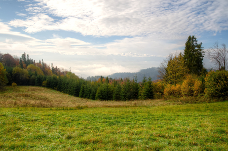 Countryside landscape. Glade in mountains in a cloudy day with hills and forest at the background Beskidy mountains Poland.