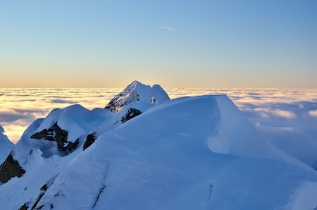 knockout: Winter mountain landscape with sea of clouds. Knockout view of snowcovered mountain peaks In Which The summits seems to be floating above the clouds. Stock Photo