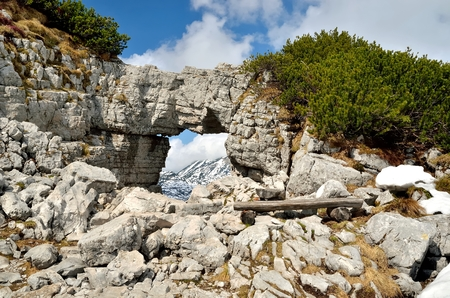 window bench: Rocky arch and bench in mountains. View over mountains from rock window in the Loser peak Dead Mountains Totes Gebirge in the Austrian Alps. Stock Photo