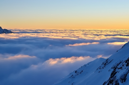 knockout: Winter mountain landscape at sunset. Knockout view of snowcovered mountain peaks and sea of clouds while the sun goes down. Stock Photo