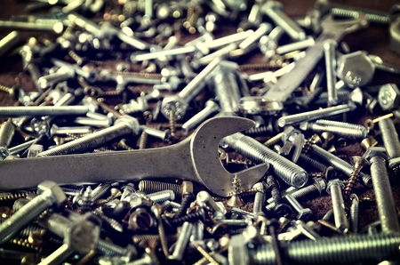 nuts and bolts: Group of screws and wrenches. Nuts bolts screws and wrenches in a pile shallow depth of field. Stock Photo