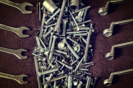 nuts and bolts: Group of screws and wrenches. Nuts bolts screws ring spanners and wrenches socket wrenches in a pile on dark background.