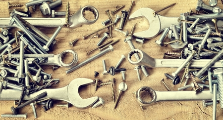 nuts and bolts: Group of screws and wrenches. Screws nuts bolts wrenches and ring spanners in a pile on natural wooden background. Stock Photo