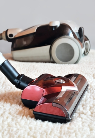 woollen: Vacuum cleaner. Close up of a modern hoover being used while vacuuming a woollen furry carpet.
