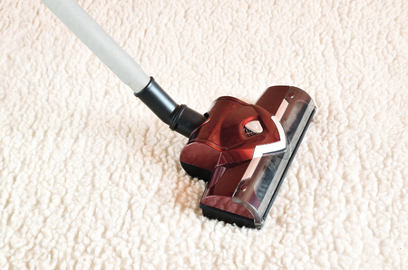 woollen: Vacuum cleaner. Close up of the head of a modern hoover being used while vacuuming a woollen furry carpet. Stock Photo