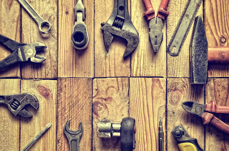 ring file: Tool frame. Wrench, ring spanner, hammer, flat file, pliers, screwdriver, monkey wrench on natural wooden background.