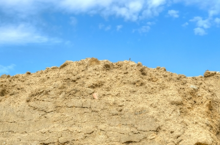 stockpile: Stockpile of sand. Pile of sand with blue sky at background.