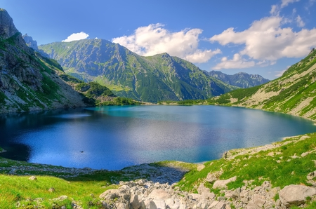 pond: Summer mountain landscape. Beautiful lake in mountains. Black Pond Black Pond under Features, lake is the most popular place in the High Tatra Mountains, Poland. Stock Photo
