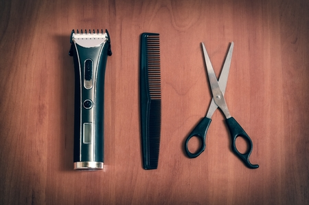 hairdressing accessories: Hairdressing accessories on a wooden table. Hair trimmer, comb and hair scissors.