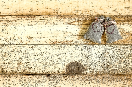 timber cutting: Small rag bags with hearts on a wooden background