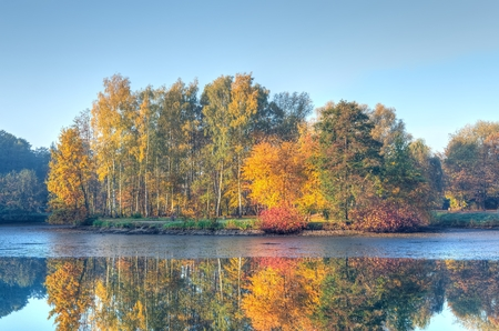 Autumn landscape. Pond and autumn colored trees in the park. Standard-Bild