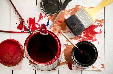 yellow paint: Brushes and paints on the white wooden floor.