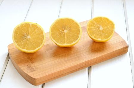 limón: Limones en una mesa de madera blanca. Limón mitades sobre una tabla de cortar.