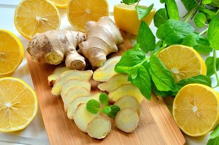 jengibre: Los limones, el jengibre y hojas de menta. mitades de lim�n, rodajas de jengibre y hojas de menta en un tablero de madera. Foto de archivo