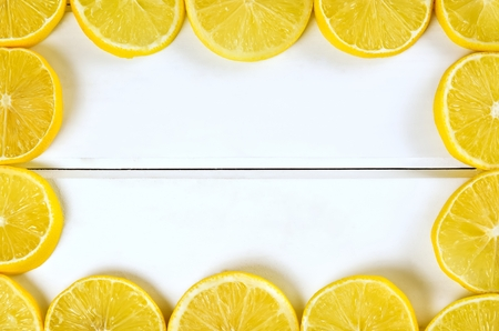 lemon juice: Lemon frame and background. Slices of lemon on a white wooden boards.