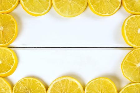 limón: Marco de limón y el fondo. Rodajas de limón sobre un fondo blanco tablas de madera.