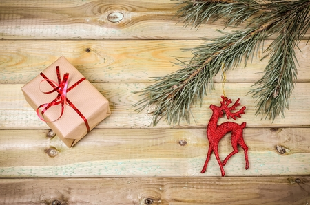 christmas ornamentation: Christmas decoration. Gift, branch of christmas tree and christmas decoration on wooden planks. Stock Photo