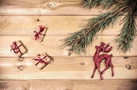 christmas ornamentation: Christmas decoration. Presents, branch of christmas tree and christmas decoration on wooden planks. Stock Photo
