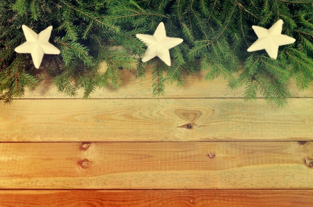 ornamentations: Christmas background. Green branches of christmas trees and white stars decorative on wooden planks.