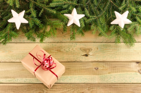 christmas ornamentation: Christmas decor. Present, branches of christmas trees and christmas decorations on wooden boards.