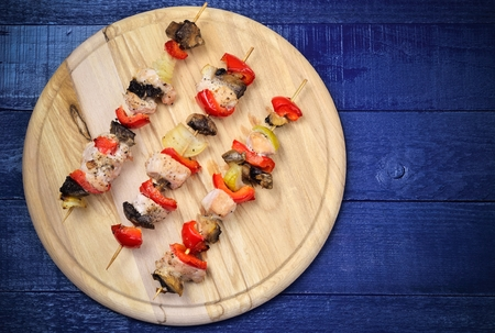 blue navy: Skewers of meat with turkey, red peppers, mushrooms and onions on a chopping board on a navy blue boards. Foto de archivo